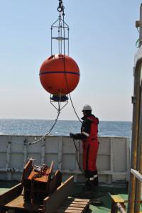 En havstømmålingsinstrument i en oppdriftskule blir sett inn i vannet.